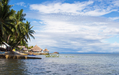 Seaside landscape with calm sea, coco palm trees lagoon and blue cloudy sky, fluffy cloud skyline