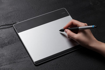 Girl draws on the black graphic tablet