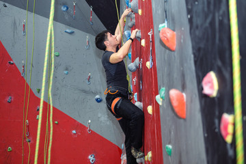 Young man climbing indoor wall and reaching the top