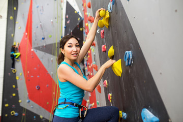 Fit sporty woman looking up at rock climbing wall at the gym and training