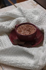 Milk chocolate in a cup on a saucer against a background of a sc