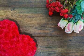 Heart shaped pillow and roses on wooden background , Valentine's day concept