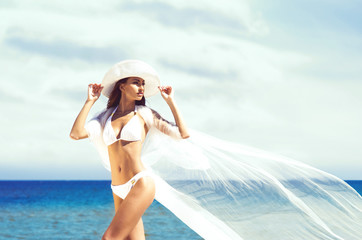 A beautiful woman in a swimsuit posing with a silk blanket on th
