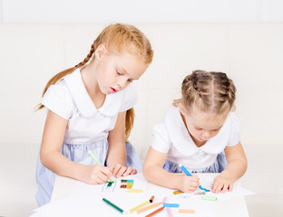 Two beautiful, cute little girls are drawing. Family, home conce