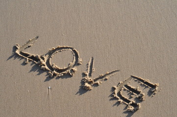 """the word """"love""""  in the sand on the beach. Valentine's concept."""