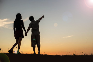 silhouette of a man and woman holding hands with each other, wa