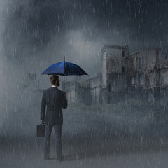 Businessman with umbrella. Black background with copyspace. Busi