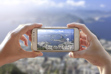 Photo camera of a smartphone. View through the screen the moment a young woman takes the picture. City of Rio de Janeiro.