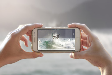 Photo camera of a smartphone. View through the screen the moment a young woman takes the picture. Surfer on a wave.