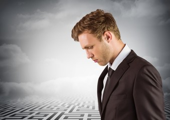 Thoughtful business man looking down with maze in background