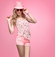 Fashion woman Having Fun. Blond Model Girl in Stylish Spring Summer Outfit Smiling. Fashion Sunglasses, Glamour Pink Shorts, Floral Top.Playful Hipster, Trendy pink fashion Hat, Wavy summer Hairstyle
