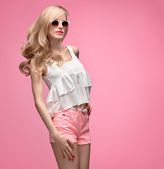 Fashion Model in Stylish Spring Summer Outfit Smiling. Blond woman Having Fun. Fashion Sunglasses, Glamour Pink Shorts. Playful Hipster, Trendy summer fashion top, Wavy Hairstyle on pink