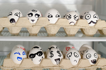 Two trays with painted smiles on the eggs on the refrigerator shelves, close up