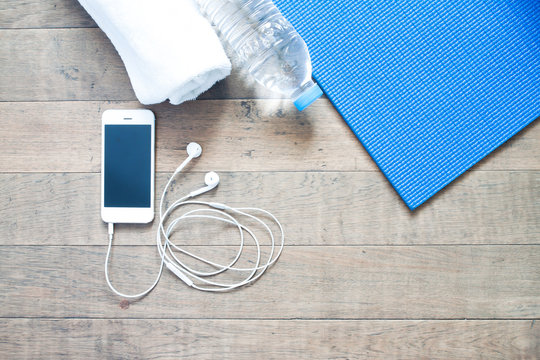 Flat lay of mobile phone with earphone and yoga mat, towel and b