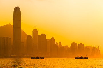 Hong Kong Evening Sky / Beautiful Hong Kong cityscape view at orange sunset light with two ships, tall buildings and Peak mountain (copy space)