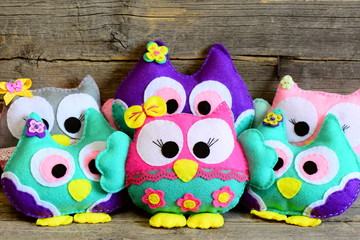 Cute children felt toys. Colorful soft owls toys on vintage wooden background. Toys crafts made of felt. Fun children background. Closeup