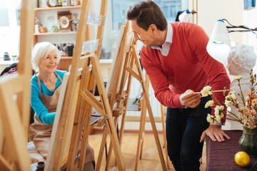 Happy artist pointing at flowers in painting studio