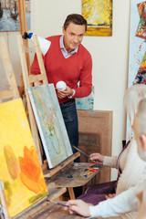 Overjoyed man teaching people in painting studio.