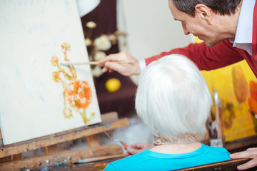 Talented artist teaching elderly woman in painting school