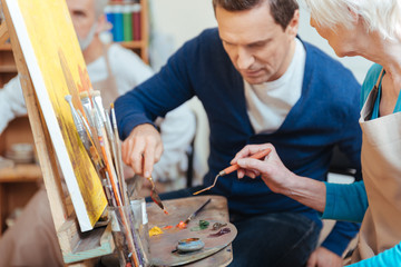 Delighted artist helping elderly woman in painting