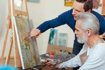 Young artist helping elderly man in painting