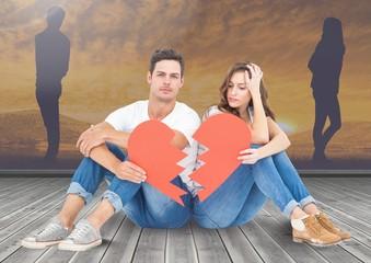 Sad couple holding broken heart