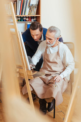 Talented artist helping elderly man in painting
