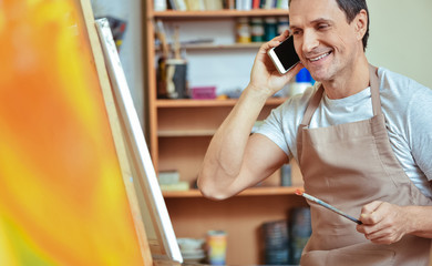 Delighted artist using cellphone in painting studio