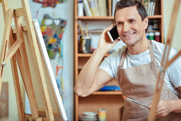 Happy artist talking on cellphone in painting studio