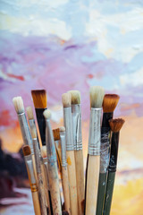 Close up of painting brushes on colorful background