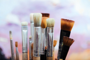 Close up of professional brushes on colorful background