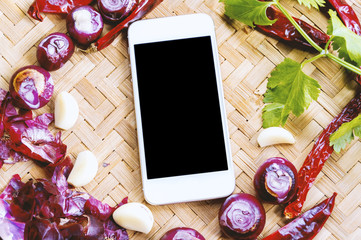 Cooking and technology. Top view smartphone with collection of fresh onions and chilis on the bamboo matt. Online recipe concept.