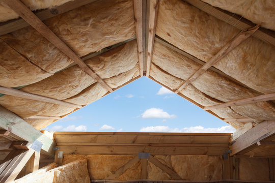 Fibreglass insulation installed in the sloping ceiling of a new frame house.