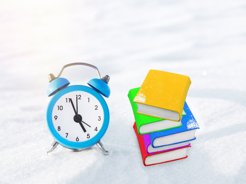 Time to read. Book and vintage alarm clock on the snow. The concept of Christmas and New Year. Magic composition. Switched to winter time. Good morning. Waiting of holiday. In anticipation of the exam