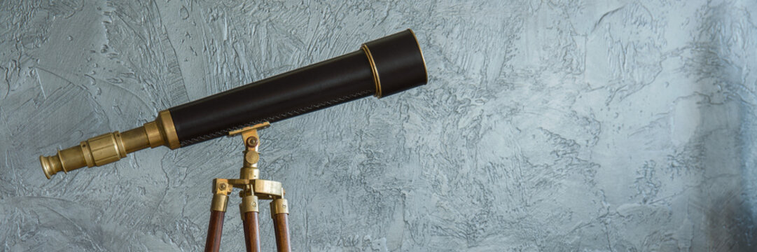 Antique telescope and grey wall