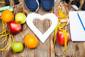 Heart, apples and oranges, diet, healthy , dumbbells  a jump rope on  wooden background