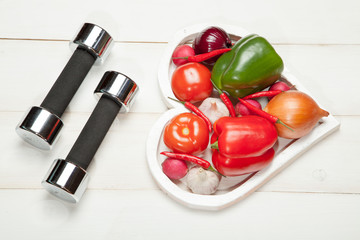 Sport and diet. Healthy lifestyle. Vegetables, dumbbells. Peppers, tomatoes, garlic, onion  radish in a heart on  white background