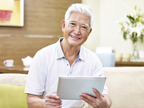 senior asian man using tablet computer