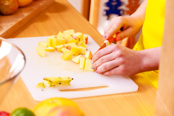 Woman housewife in kitchen cutting apple fruits
