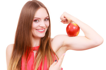 Woman fit girl holds apple fruit on her biceps arm