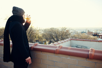Man looking at view of city, smoking a cigarette and drinking, Park Slope, Brooklyn, New York, United States of America