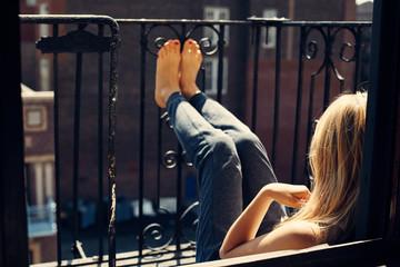 Woman sitting on balcony, bare feet against railings, Brooklyn, New York, United States of America
