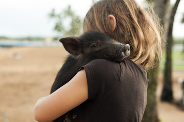 Young child carrying black piglet