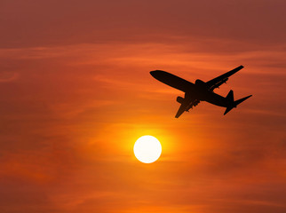 Silhouette passenger airplane flying away in to sky high altitude above the sun during sunset