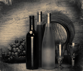 bottle of wine and wooden barrel for wine on a wooden table, black and white vintage photograph