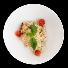 Creamy risotto in porcelain plate isolated on black