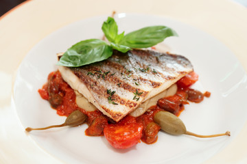 Sea bass fillet with tomato sauce and capers