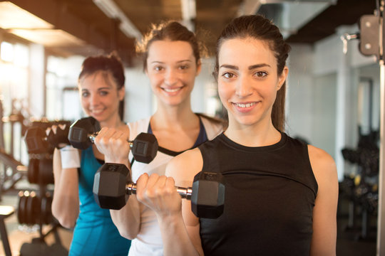 Three fit and beautiful young women lifting weights in a fitness club. Focus on the first girl in front.