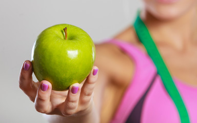 woman fit girl with measure tape and apple fruit