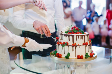 Waiter takes a piece of wedding cake while bride and groom cut i